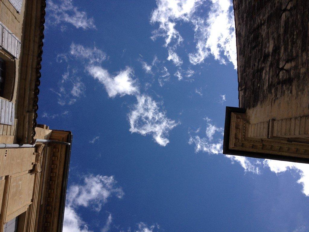 Ciel bleu et nuages entre deux maisons